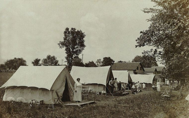 A row of four tents set up in a clearing, with small houses in the background. A woman stands in the opening of the first tent; a wooden chair is beside her. Families pose at the openings of the other tents.