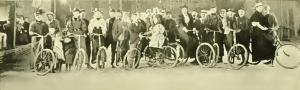 Image of beginning riders posing with their bikes in the Bicycle School circa 1896