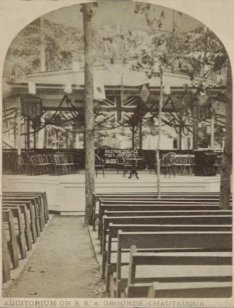 Black and white photo of the open-air Auditorium from the back. The audience benches have backs on and they face a raised platform stage.