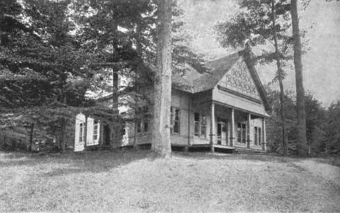 Black and white photo of a building with aa large front porch and gingerbread trim, set among tall trees.