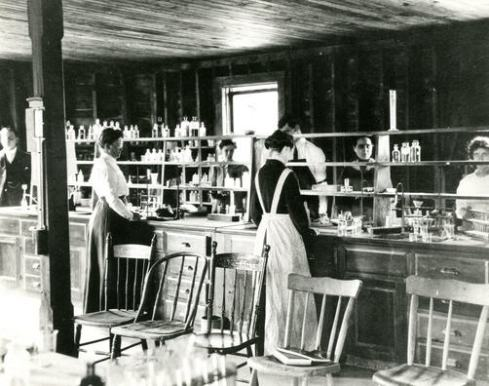 Black and white photograph of women standing at lab desks and shelves stocked with bottles and beakers