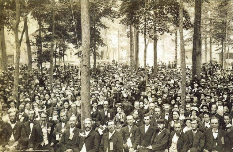 Black and white photograph of men and women seated in the Auditoriam amid the trees