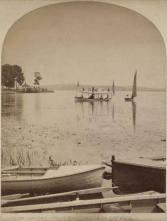 Old black-and-white photo of small boats on Lake Chautauqua off the shore of Fair Point with Point Chautauqua in the distance