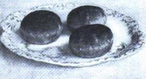 Black and white photo of three individual cakes arranged on a plate.