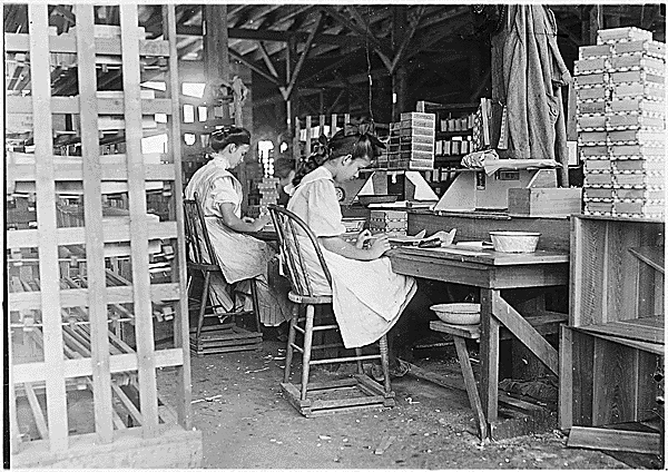 A young girl working alongside a woman in a paper box factory, 1912. From National Archives.