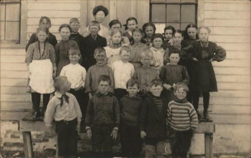 Undated photo of a teacher and her class.