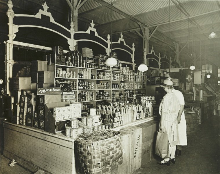 Customers shopping for canned goods at a grocery in the early 1920s