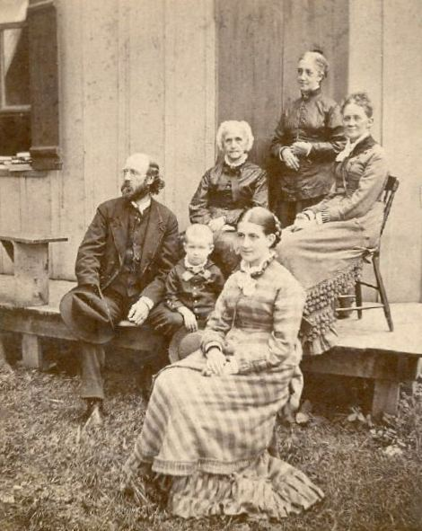 1875 photo of Isabella, her husband and son seated on a wooden porch of a house. Behind them are seated Isabella's mother, her sister Julia, and an unidentied woman.