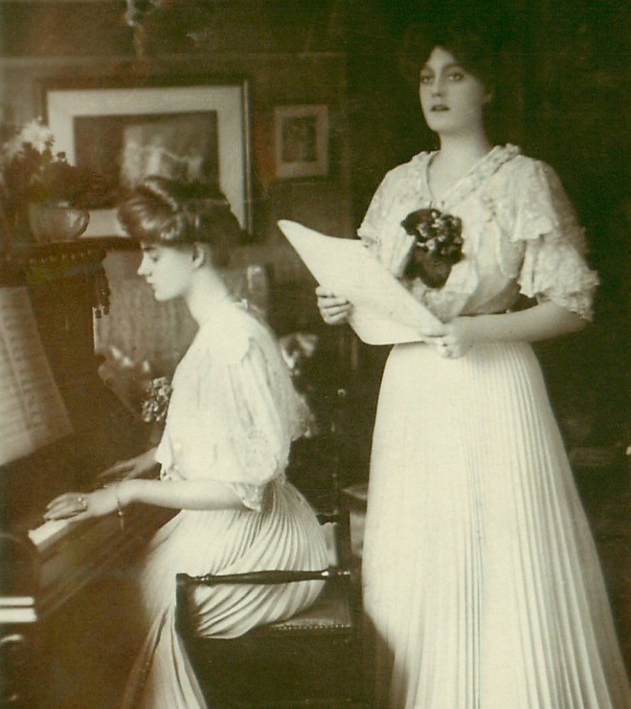 A young woman stands holding sheet music and singing. Beside her another young woman is seated, playing a piano.