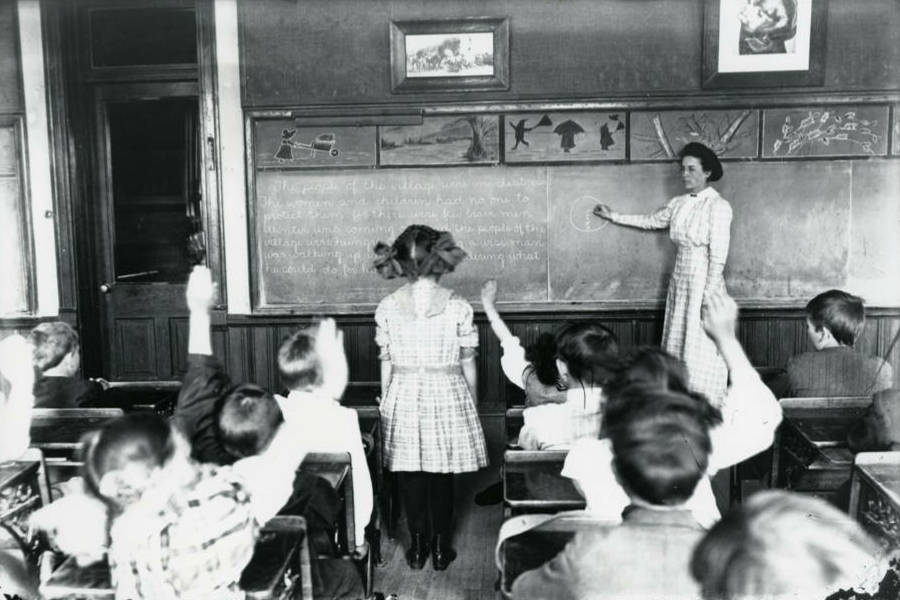 Photo dated about 1910. A teacher stands at the classroom blackboard where words and shapes are drawn, and points to one section of the blackboard. One little girl stands facing the teacher (her back to the camera) to answer the teacher's question. All other students sit at desks with their backs to the camera. Some students have their hands raised to answer the question.