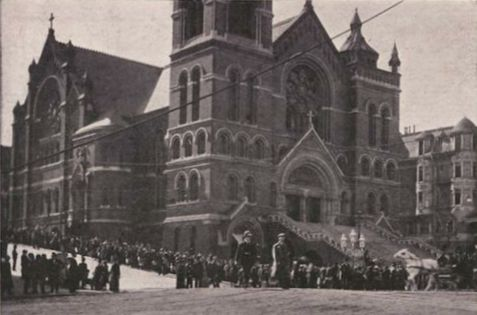 Lines of people stand outside a large cathedral.