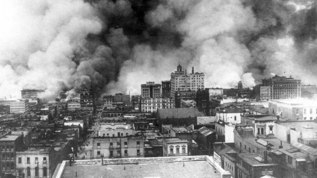 Black and white photo of smoke billowing up from the burning city.