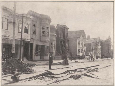 Black and white photo of houses damaged in the quake. The paved road in front of the homes is buckled.