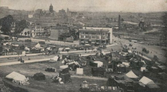 A group of tents and make-shift homes set up in an open park with a few nearby partially-collapsed buildings. In the background the tall downtown buildings have disappeared; only a single dome stands out against the skyline.