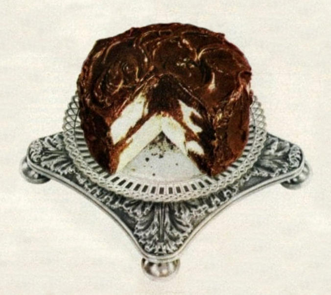 Photo of a chocolate-iced marble cake on an ornate silver serving stand.