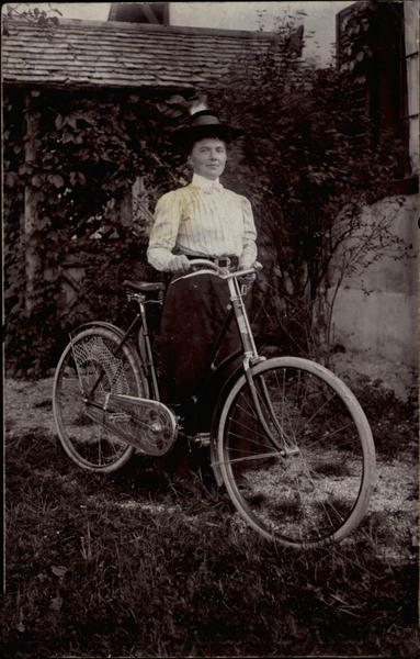 Photograph dated 1912 of woman standing beside her bicycle. She is wearing a long skirt, long-sleeved shirt with high collar, and a bonnet.