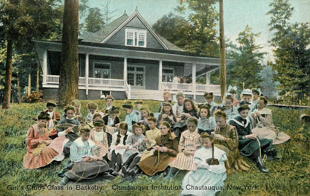 A group of about thirty girls sit on the grass. Each girl weaves a holds a length of straw or small