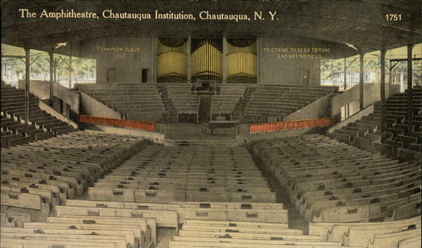 Photo of the inside of the amphitheatre, a large wood structure with a stage at one end with about 12 rows of raised seating behind. The floor and 3 remaining sides of the theatre are filled with rows of wooden benches.