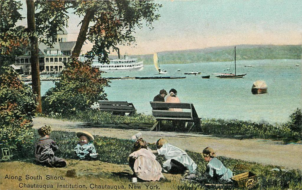 A group of small children play in the grace near the lake shore. A couple sits on a wooden bench, looking about upon the lake, where there are sail boats, row boats and a steamer.