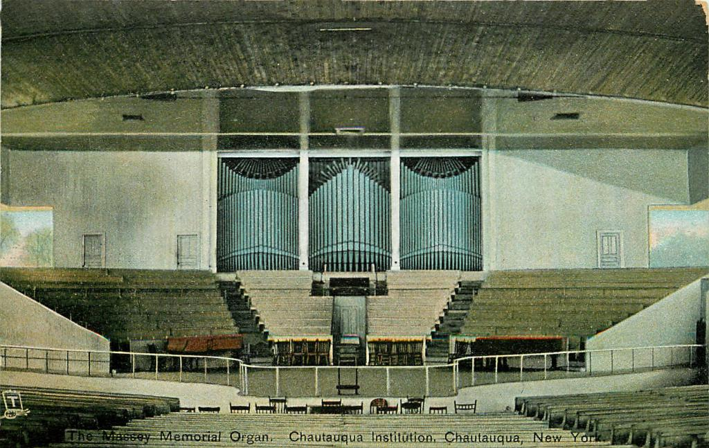 Photo of the amphitheatre stage. In the middle is an elevated platform for the organist and three large banks of organ pipes.